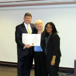 (Courtesy Photo) At-large City Councilor John Connolly presents a resolution supporting the Boston Latin School Youth Climate Action Network (BLS Youth CAN) program to JP resident and program co-president Eshe Sherley (right) at the school on Aug. 11. Joining them is faculty advisor Cate Arnold (center).