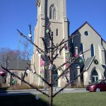 "(Gazette Photo by John Ruch) A ""Jesse Tree"" representing the Christian tradition of Advent and decorated by community members stands outside the First Baptist Church in Jamaica Plain at 633 Centre St. last week. The metal structure was created by JP's Stonybrook Fine Arts."