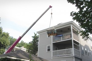 A piano is removed from the third-floor porch of a home at 115 Williams St. by a Gentle Giant Moving Company crane on Aug. 22. (Photo by Jennifer Uhrhane)