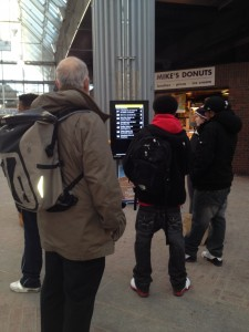 Passengers check the bus countdown clock at Forest Hills T Station on Feb. 11. (Gazette Photo by Rebeca Oliveira)